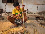 11 MARCH 2016 - LUANG PRABANG, LAOS:   A man trims bamboo to make traditional musical instruments in the community of Chomphet, across the Mekong River from Luang Prabang. Laos is one of the poorest countries in Southeast Asia. Tourism and hydroelectric dams along the rivers that run through the country are driving the legal economy.     PHOTO BY JACK KURTZ