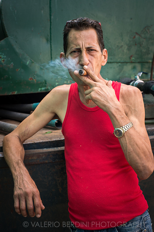 A man working with a water truck puffs a cigar in a break while a tank is being filled. Santa Clara, Cuba.