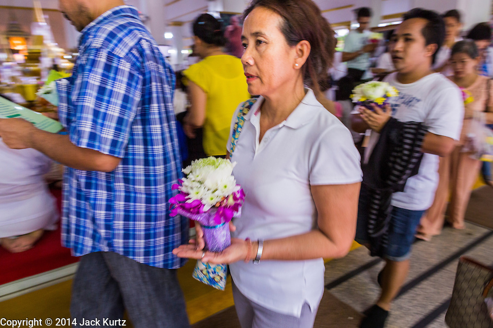 11 JULY 2014 - BANGKOK, THAILAND: Thai Buddhists carry flowers around the main prayer hall Wat Pathum Wanaram for Asalha Puja Day. Asalha Puja is the day the Lord Buddha preached his first sermon to followers after attaining enlightenment. The day is usually celebrated by merit making and listening to a monks' sermons. It is also day before the start of the Rains Retreat, the three month period when monks stay in their temple for intense mediation and spiritual renewal.    PHOTO BY JACK KURTZ