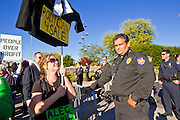 30 NOVEMBER 2011 - PHOENIX, AZ:    Anti-ALEC protesters pass Phoenix police in front of the Westin Kierland Resort and Spa Wednesday. About 300 people picketed the American Legislative Exchange Council (ALEC) conference at the Westin Kierland Resort and Spa in Phoenix, AZ, Wednesday. The protesters claim ALEC, a conservative think tank, violates its tax exempt status by engaging in lobbying, a charge ALEC officials deny. Many conservative pieces of legislation, like Arizona's anti-immigration bill SB1070, originate with ALEC conferences (SB 1070 originated at an ALEC conference several years ago). Many of the protesters are also members of the Occupy movement.    PHOTO BY JACK KURTZ