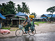14 JUNE 2013 -  SAMALAUK, AYEYARWADY, MYANMAR: A couple rides a bicycle through the rain along Highway 5 in Samalauk, Ayeyarwady, in the Irrawaddy delta region of Myanmar. This region of Myanmar was devastated by cyclone Nargis in 2008 but daily life has resumed and it is now a leading rice producing region.   PHOTO BY JACK KURTZ