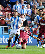 Picture by Graham Crowther/Focus Images Ltd. 07763140036.10/9/11 .John Welsh of Tranmere slides in on Calum Woods of Huddersfield  during the Npower League 1 game at the Galpharm Stadium, Huddersfield.