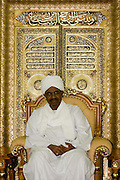 Sudanese President, Omar Hassan Ahmad al-Bashir is seated against a gold leaf backdrop of Islamic texts in a reception room of his palace in central Khartoum. Al Bashir is head of the National Congress Party and has been in power since October 1993.