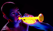 Young man with puffy cheeks playing a glowing trumpet.Black light