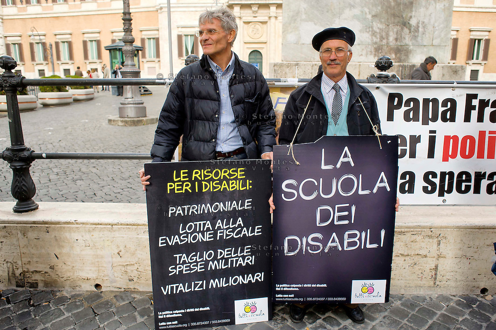 Roma 5 Novembre 2014<br /> Manifestazione davanti al Parlamento, dell'associazione, &quot;Tutti a scuola&quot;, per protestare contro  legge di stabilit&agrave; del Governo Renzi, che taglia i  fondo nazionale della non autosufficienza e   cancella i diritti dei disabili. I manifestanti  portano una ghigliottina per decapitare simbolicamente i politici. <br /> Rome November 5, 2014 <br /> Demonstration in front of the Parliament of the association &quot;Everybody to School&quot; to protest against the law of stability of the  Prime Minister Renzi's government, which cuts the bottom of national self-sufficiency and cancels out the rights of the disabled. Protesters carry a guillotine to decapitate symbolically politicians.