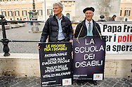 "Roma 5 Novembre 2014<br /> Manifestazione davanti al Parlamento, dell'associazione, ""Tutti a scuola"", per protestare contro  legge di stabilità del Governo Renzi, che taglia i  fondo nazionale della non autosufficienza e   cancella i diritti dei disabili. I manifestanti  portano una ghigliottina per decapitare simbolicamente i politici. <br /> Rome November 5, 2014 <br /> Demonstration in front of the Parliament of the association ""Everybody to School"" to protest against the law of stability of the  Prime Minister Renzi's government, which cuts the bottom of national self-sufficiency and cancels out the rights of the disabled. Protesters carry a guillotine to decapitate symbolically politicians."