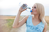 Beautiful woman drinking water from bottle while standing on field