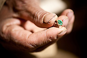 An Afghan miner holds a piece of emerald.