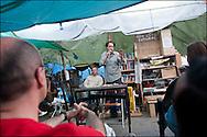 """Un debat a lieu autour d'un intervenant dans la bibliotheque du camp. // Le mouvement spontane du """"15 M"""" (15 mai) compose de citoyens espagnols campe depuis 2 semaines sur la place Puerta Del Sol avec pour revendication la construction d'une democratie nouvelle. Organise en commission les citoyens prennent la parole lors d'assemblee ouverte a tous - Place Puerta Del Sol à Madrid le Juin 2011. ©Benjamin Girette/IP3Press"""
