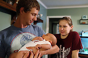 Brandon Kennedy holds his son Paxton as Melissa Kennedy looks on Wednesday at their home in Vina. The Kennedys, who live close to an hour away from the hospital where Paxton was delivered, decided to induced labor to ease the stress of potential issues due to the fact that they live so far from the hospital.