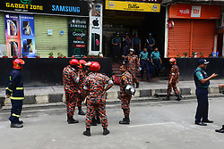 March 29, 2019 - Dhaka, Bangladesh - Bangladeshi police and firefighters stand guard near the burnt building in Dhaka, Bangladesh, on March 29, 2019, a day after flames tore through the 22-storey FR Tower. - The death toll from a horrific blaze that ripped through a Bangladesh skyscraper rose on March 29 to 25 victims, including some who leapt to their deaths, as firefighters combed through the charred shell of the building. (Credit Image: © Str/NurPhoto via ZUMA Press)