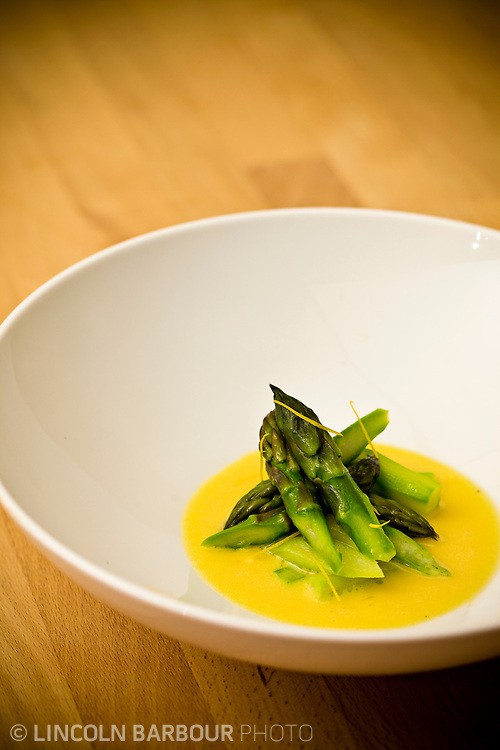 Asparagus tips in served with Butter Sauce in a bowl