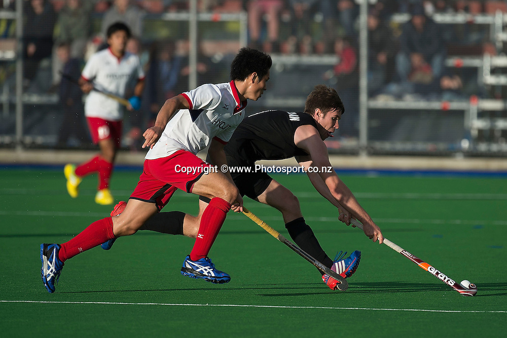 James Coughlan (R of New Zealand dribbles the ball with Miyu Tanimitsu of Japan in defense during the Black Sticks Men v Japan international hockey match at the Coastlands Kapiti Sports Turf in Paraparaumu on Saturday the 22nd of November 2014. Photo by Marty Melville/www.Photosport.co.nz