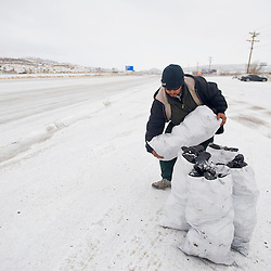 121912       Brian Leddy.Juan Guerra sells coal on the side of Historic Route 66 Wednesday morning. Along with snow and ice, the winter storm brought sub-zero temperatures.