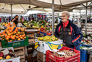 Older Roman woman selling fruit at Campo De Fiori open air market in Rome, Italy, with colorful tangerines, bananas, and walnuts.