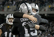Dec 17, 2017; Oakland, CA, USA; Oakland Raiders quarterback Derek Carr (4) celebrates after Oakland Raiders wide receiver Michael Crabtree (15) scored a touchdown against the Dallas Cowboys during an NFL football game at Oakland-Alameda County Coliseum.