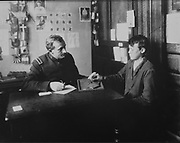 Immigration officer carrying out a psychological assessment on a young immigrant to establish his socio-psychological profile, needed for his admission file, in the Legal Inspection room, photograph, c. 1914, displayed in the Ellis Island Immigration Museum, in the main building on Ellis Island, the immigration processing centre for the United States from 1892 to 1954, at the mouth of the Hudson river in New York City, NY, USA. Ellis Island and its Immigration Museum are part of the Statue of Liberty National Monument and are managed by the National Park Authority. Picture by Manuel Cohen