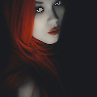 Young adult female with long red hair and lipstick looking at camera with pale face