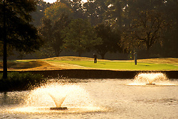 Stock photo of fountains in a golf course pond at sunset