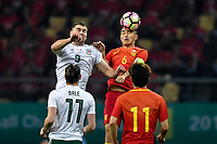 Feng Xiaoting, top, of Chinese national men's football team heads the ball to make a pass against Sam Vokes of Wales national football team in the semi-final match during the 2018 Gree China Cup International Football Championship in Nanning city, south China's Guangxi Zhuang Autonomous Region, 22 March 2018.