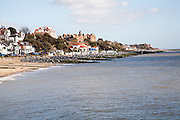 Sandy beach rock armour sea defences and historic buildings on the seafront on a sunny day in winter at Felixstowe, Suffolk, England