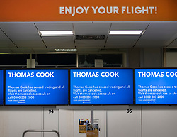 CAPTION CORRECTION © Licensed to London News Pictures. 23/09/2019. Gatwick, UK. A sign says 'ENJOY YOUR FLIGHT' above closed Thomas Cook check-in desks at Gatwick Airport after the travel firm collapsed. The 178 year old travel operator has gone in to liquidation after rescue talks failed overnight. This will trigger the largest peacetime repatriation as more than 150,000 British holidaymakers will need to be brought home. Photo credit: Peter Macdiarmid/LNP