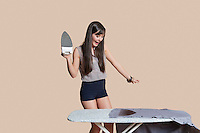 Shocked young woman looking at burnt shirt on ironing board over colored background