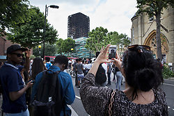 © Licensed to London News Pictures. 18/06/2017. London, UK. A woman takes a photo of the burnt out remains of Grenfell tower block . The blaze engulfed the 27-storey building killing dozens - with 34 people still in hospital, many of whom are in critical condition. The fire brigade say that they don't expect to find anyone else alive. Photo credit: Peter Macdiarmid/LNP