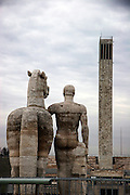 A classical equestrian statue faces one of the numerous stone towers near the Olympic Stadium in Berlin, Germany.