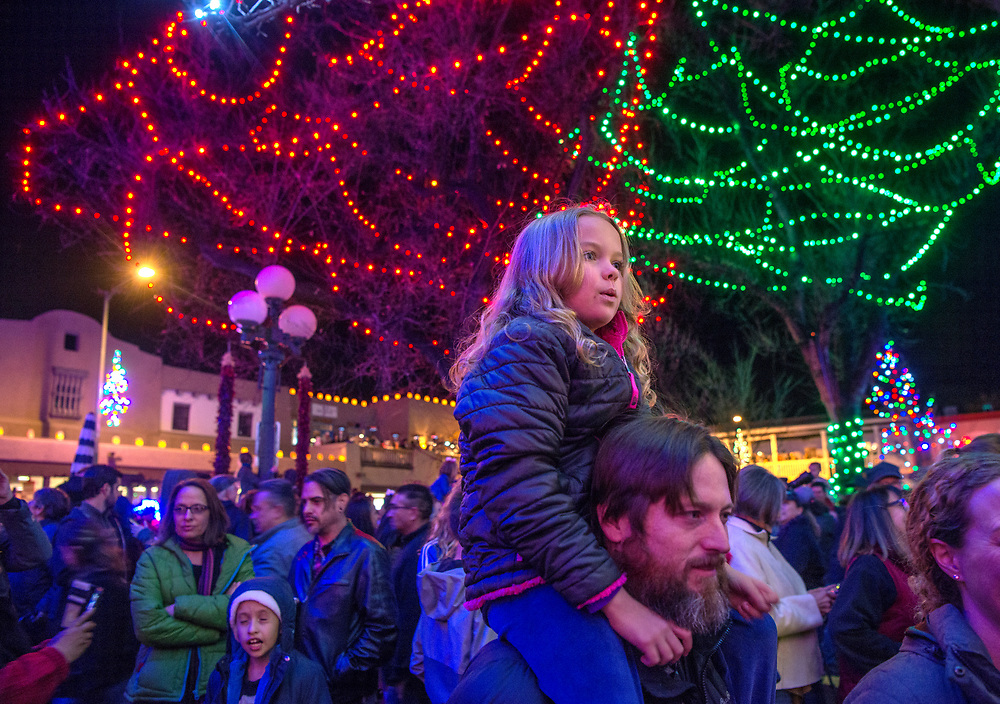 em112417b/b/Maggie Lytle, 9, sits on Brady Scott's shoulders to see the Chirstmas lights on the Santa Fe Plaza Friday November 24, 2017. This was after the annual celebration to turn on the holiday lights. There were more than 10,000 lights and 1000 faralitos lighting the Plaza. (Eddie Moore/ Albuquerque Journal)