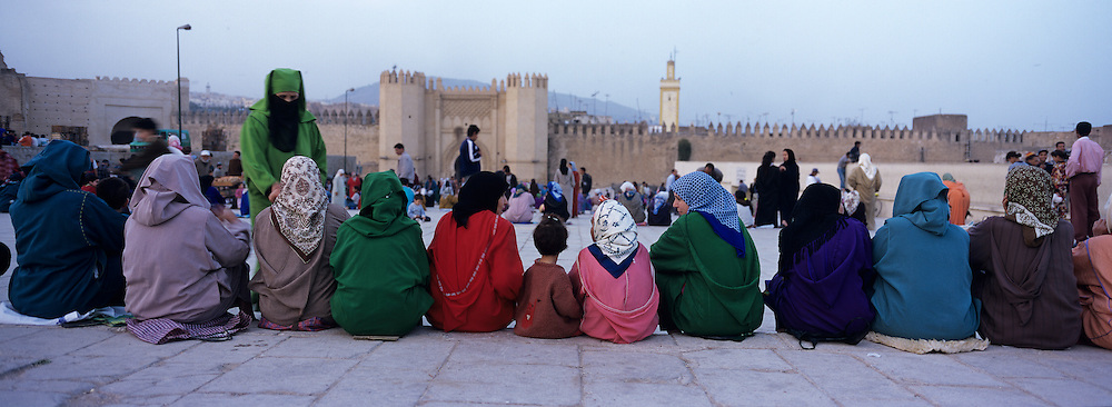 Africa, Morocco, Line of women sit on steps outside gate of Bab Boujeloud in walled medina in city of Fez at sunset