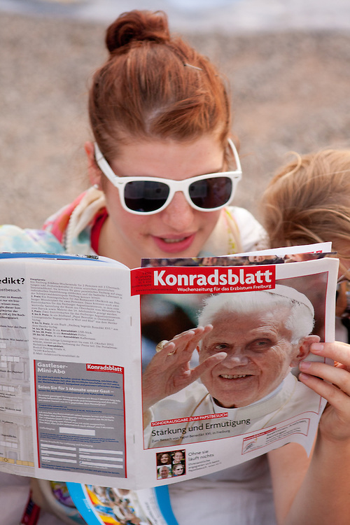 Freiburg, Germany. September 24, 2011. A teenager reads about the visit of Pope Benedikt XVI in Freiburg on Saturday. Photo: Miroslav Dakov