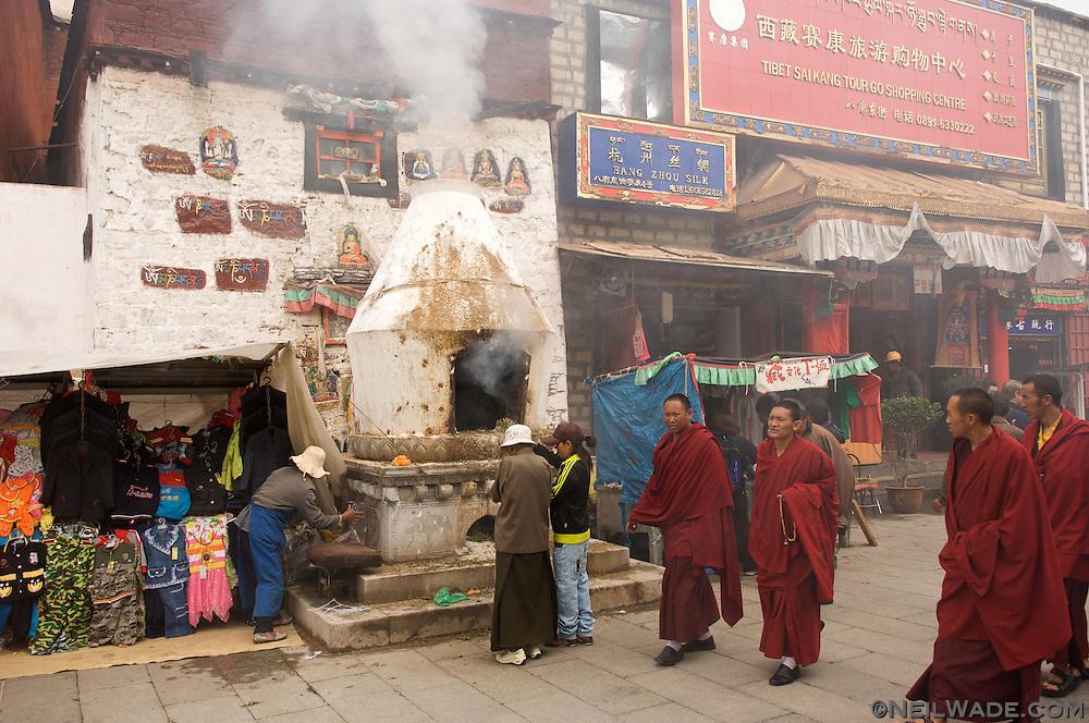 Tibetan monks pass an juniper burner on the Barkor in Lhasa, Tibet.