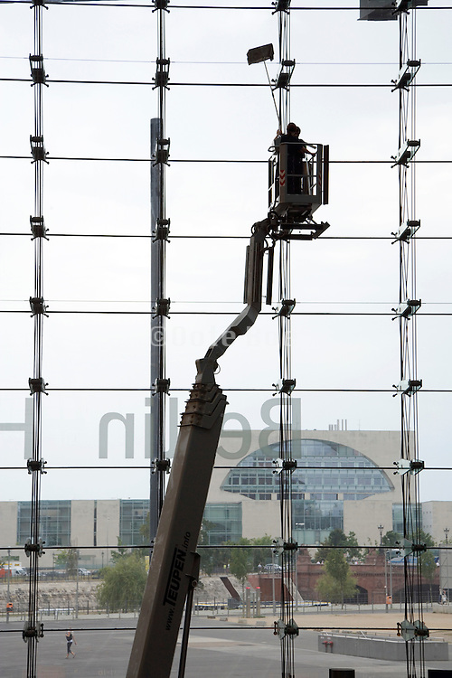 window cleaners at work on the large glass wall at the Hauptbahnhof train station in Berlin