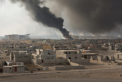 Licensed to London News Pictures. 02/11/2016. Qayyarah, Iraq. Smoke and flames rise from burning oil welsl, set alight by retreating Islamic State militants, located with the Iraqi town of Qayyarah.<br /> <br /> Two months after being liberated from the Islamic State, the Iraqi town of Qayyarah, located around 30km south of Mosul, is still dealing with the environmental repercussions of their ISIS occupation. The town's estimated 15,000 inhabitants constantly live under, and in, heavy clouds of smoke which often envelope the settlement. The clouds emanate from burning oil wells in a nearby oil field that were set alight by retreating ISIS extremists after a two year occupation. The proximity of the fires, often right next to homes within the town, covers many buildings and residents with thick soot and will lead to long term health and environmental implications. Photo credit: Matt Cetti-Roberts/LNP