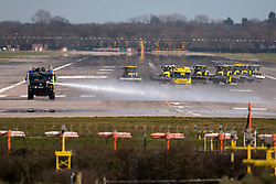 © Licensed to London News Pictures. 29/02/2016. Gatwick, UK. A fire vehicle spraying liquid over an area of spillage as tractors with cleaning equipment wait to clean the runway at Gatwick Airport in West Sussex, where the main runway has been closed due to a spillage. Photo credit: Peter Macdiarmid/LNP
