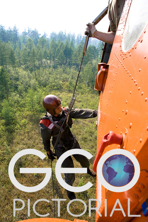 A Russian smoke-jumper abseils out of a helicopter near the site of a wild fire in a remote region of the SIberian Taiga Boreal forest;
