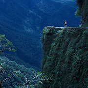 "Mountain Biking on Death Road, Bolivia...A tour group of Mountain Bikers bike down the infamous narrow dirt road, most of the road no wider than 3.2 meter's, is cut into the side of the mountain with sheer drops to the left of up to 600 meter's with virtually no safety rails on the winding steep decent....The North Yugas Road is a 64 Kilometer road leading from La Paz to Corioico. It is legendary for it's extreme danger and in 1995 the Inter American Development Bank christened is as the ""world's most dangerous road"".. The road was built in the 1930's during the Chaco War by Paraguayan prisoners to connect the Amazon rainforest region of Northern Bolivia to it's capital City La Paz. One estimate is that 200 to 300 travelers were killed yearly along the road. On 24 July 1983, a bus veered off the Yungas Road and into a canyon, killing more than 100 passengers in what is said to be Bolivia's worst road accident..A new stretch of the La Paz-Coroico highroad was opened in 2006 to bypass the notorious stretch known as death road..The danger of the road has now made it a popular tourist destination starting in the 1990's and drawing thrill-seekers and mountain bike enthusiasts who ride on the 64km mainly downhill stretch from La Cumbre, a 4,700 meter peak to Yolosa, a decent of 3600 meter's (11,800 feet). The journey includes breathtaking views of snow covered peaks and towering cliffs and starts along modern asphalted road before entering the jungle itself and the most dangerous and notorious part of the ride. The infamous narrow dirt road, most of the road no wider than 3.2 meter's, is cut into the side of the mountain with sheer drops to the left of up to 600 meter's with virtually no safety rails on the winding steep decent..There are now many tour operators catering to this activity, providing information, guides, transport and equipment. Nevertheless, the Yungas Road remains dangerous. At least 13 of these cyclists died on the ride since 1998, the latest A 28-year-o"