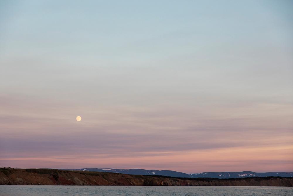 Canada, Newfoundland, Codroy, Full moon rises above cliffs along Atlantic Ocean shoreline at sunset on summer evening