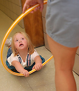 Marissa dube, 5, holds onto the hoola-hoop while she lays on her stomach on a scooter that is pulled by her Physical Therapist Amy Metrena.  The kids are in summer school to keep them up to date with their skills during the summer