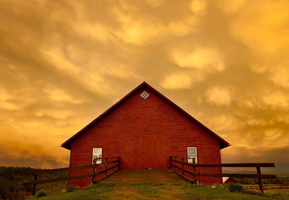 Dramatic sunset clouds as a thunderstorm clears with red barn in foreground, East Montpelier, Vermont