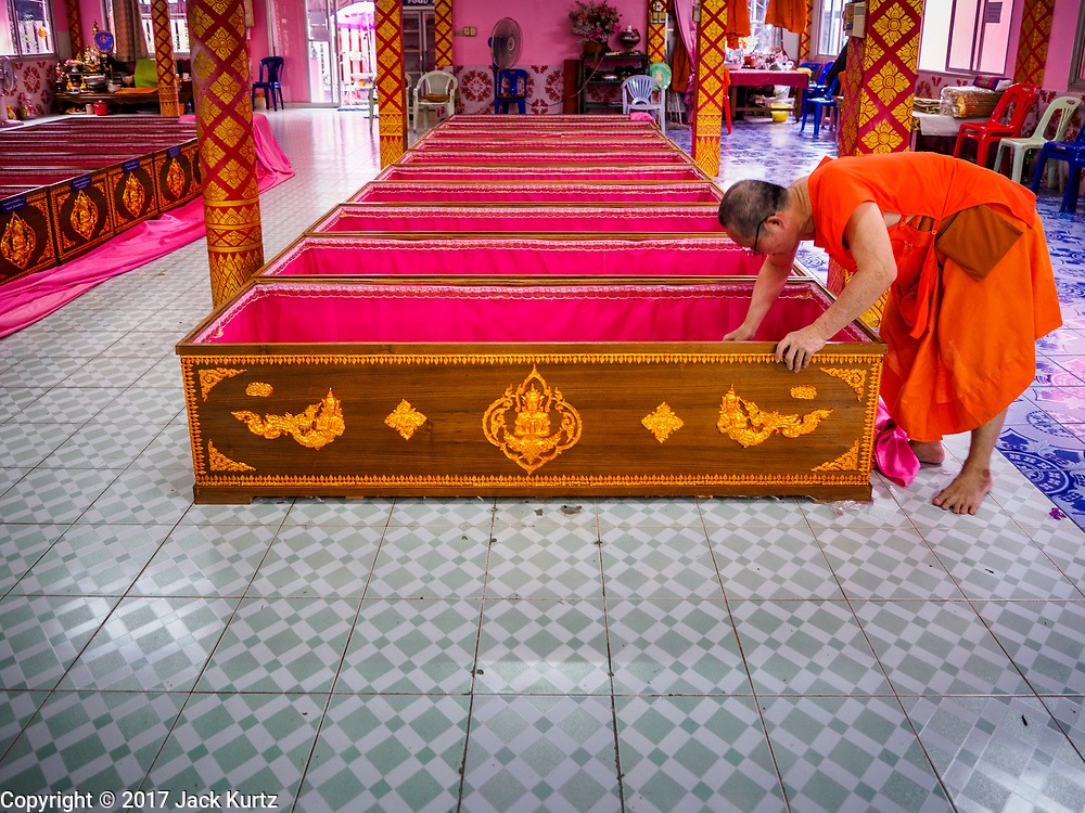 """29 MARCH 2017 - BANG KRUAI, NONTHABURI, THAILAND:  A Buddhist monk picks up money left in a coffin as a donation after a """"Resurrection Ceremony"""" at Wat Ta Kien (also spelled Wat Tahkian), a Buddhist temple in the suburbs of Bangkok. People go to the temple to participate in a """"Resurrection Ceremony."""" Groups of people meet and pray with the temple's Buddhist monks. Then they lie in coffins, the monks pull a pink sheet over them, symbolizing their ritualistic death. The sheet is then pulled back, and people sit up in the coffin, symbolizing their ritualist rebirth. The ceremony is supposed to expunge bad karma and bad luck from a person's life and also get people used to the idea of the inevitability of death. Most times, one person lays in one coffin, but there is family sized coffin that can accommodate up to six people. The temple has been doing the resurrection ceremonies for about nine years.         PHOTO BY JACK KURTZ"""