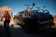 Riders shuttle bikes and gear through the canyon as the sun sets during a tour of the White Rim Trail near Moab, Utah.