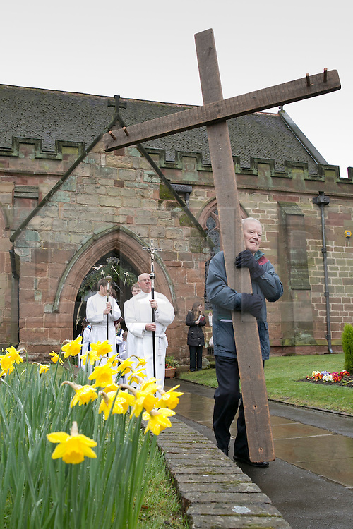 """© Licensed to London News Pictures. 3/4/2015. Solihull, West Midlands, UK. The Good Friday """"Walk of Witness"""" taking place in Solihull. People of all faiths congrgate outside St Alphege Church and walk the short distance to Mell Square to hold a multi-faith prayer meeting. Pictured, The cross begins it's journey through Solihull. Photo credit : Dave Warren/LNP"""
