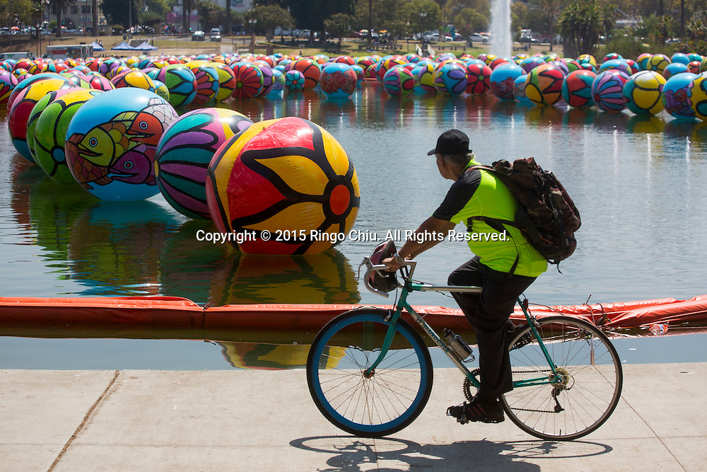 A cyclist rides past the hand-painted vinyl balls floating in the MacArthur Park Lake as part of a large-scale public arts installation organized by the Portraits of Hope charity in Los Angeles, California on August 26, 2015. The work titled ``The Spheres at MacArthur Park,'' involves filling the park's 8.39-acre lake with about 3,000 balls, each 4 to 6 feet in diameter and covered in bright floral and fish patterns. (Photo by Ringo Chiu/PHOTOFORMULA.com)