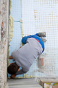 young man placing insulation before poring concrete