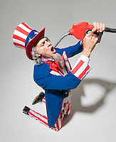 Uncle Sam on knees holding gasoline nozzle above his open mouth..Model Release: 20080626_MR_A