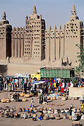 The mud-walled Great Mosque in the African city of Djenne, in Mali was built decades ago on the ruins of a 13th-century mosque. It is often a location for temporary markets and sales people. Material World Project.