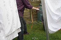 Mowing the lawn beside a clothes line with bed linen, compost bin in background
