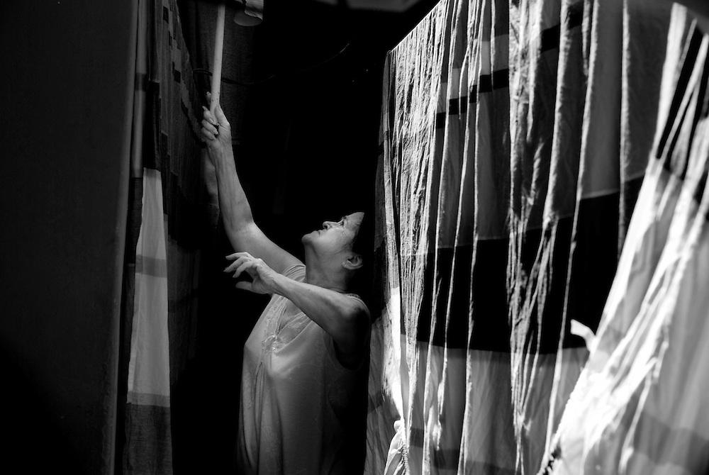 APUNTES SOBRE MI VIDA: LA PASTORA I - 2009/10<br /> Photography by Aaron Sosa<br /> Carmen Cecilia Rojas, Mama recogiendo la ropa seca.<br /> La Pastora, Caracas - Venezuela 2009<br /> (Copyright &copy; Aaron Sosa)